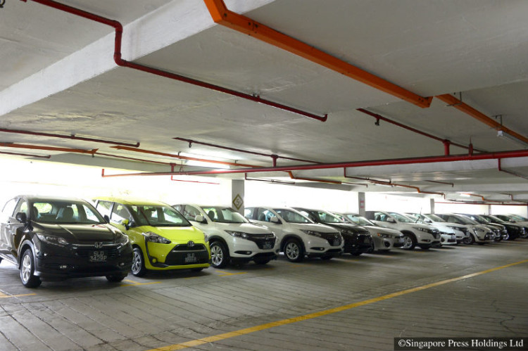Private-hire cars at a multi-storey carpark near Beach Road on Wednesday. The number of such cars, used for picking up paying fares, is catching up with the total number of taxis owned by cab firms.