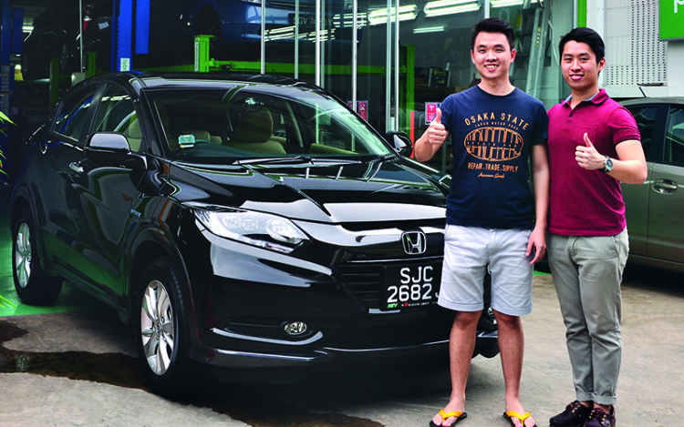 Jonathan (in red) handing a Honda Vezel Hybrid back to a satisfied customer.