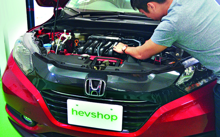 Jonathan inspects a brand new hybrid vehicle.