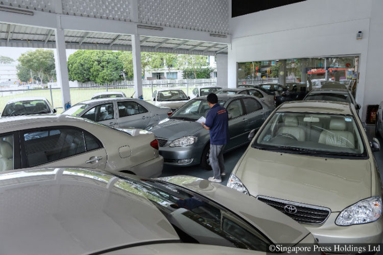 An employee from a rental car company checking the condition of a car among a fleet of cars at its premises on 4 February 2013.