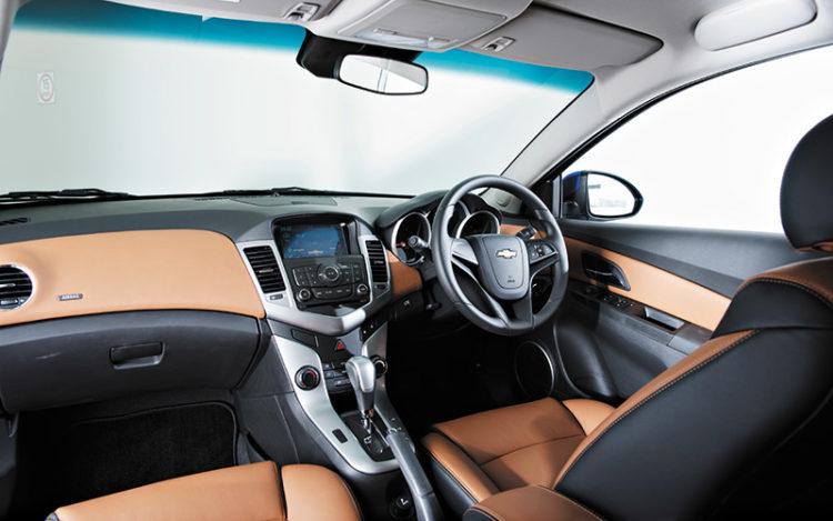 "CRUZE - Compared to the others, cockpit is more snug and glovebox is about one-third smaller. Start/stop button is too ""hidden"". Seats are better bolstered than in the Kia and Hyundai, and the door handles and indicator stalks feel more substantial."