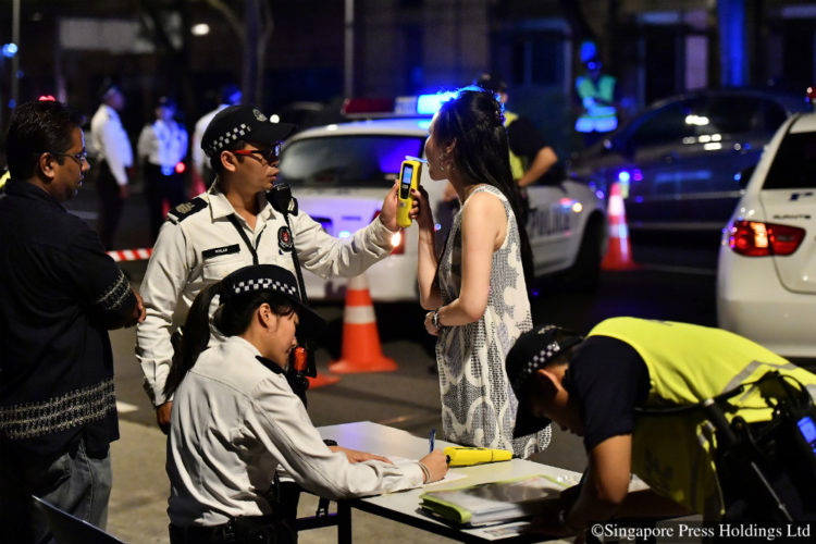 A motorist suspected of drink-driving being tested using a hand-held breath analyser. Police held an islandwide enforcement operation targeting errant motorists from midnight to 3am along Clemenceau Ave opposite Singapore Shopping Centre on 20 October 2016.