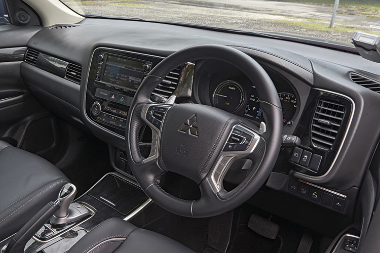 Outlander PHEV's high-tech cockpit has hybrid-specific displays and a joystick-like gearshift lever, but ironically, no electric parking brake.